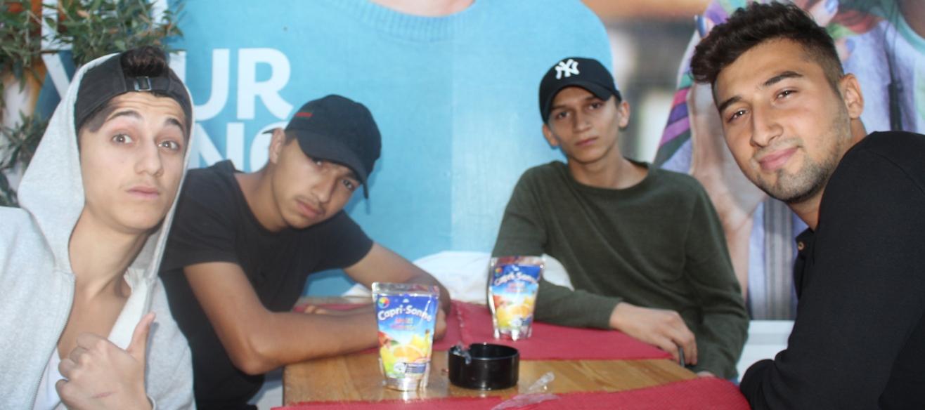 Vier junge Männer sitzen an einem Tisch und schauen in die Kamera