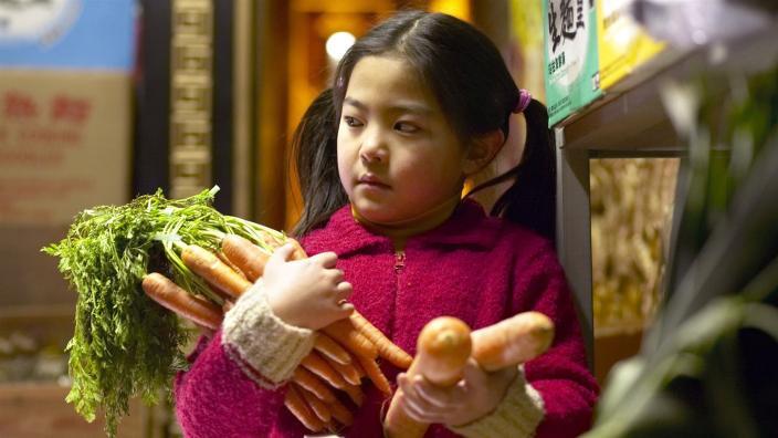 Mädchen mit einem Bund Möhren im Arm. Filmbild aus Winky will ein Pferd